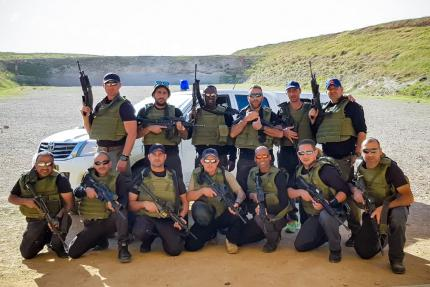 Group shot of cadets in bulletproof vests armed with M16 assault rifles against a background of a special forces vehicle, training center, Israel